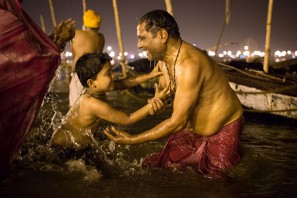 A father encourages his son to take a holy bath in the  cold water of the sacred river Ganga, India.