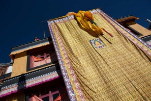 A wall covering representing Buddha is hanged on the top of the monastery.