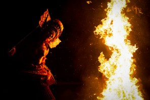 The Theyyam artist dancing around the fire.