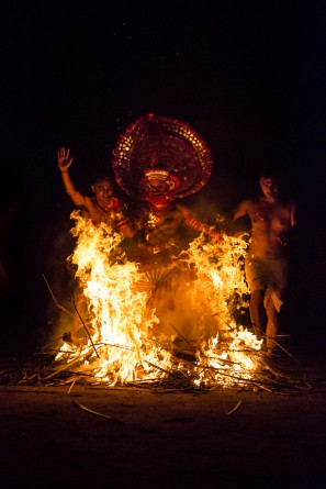 The Theyyam artist, now in a state of trance, is walking through fire with the priests who assist him.